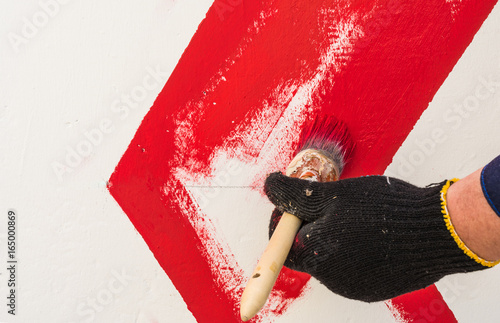 The hand in the black glove holds the brush