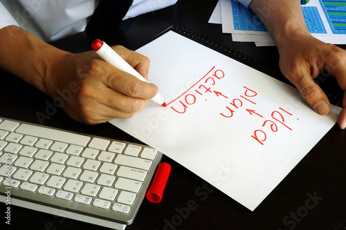 Businessman is writing Idea – plan - action sign on a note.