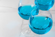 Alcohol drink. Glasses with trendy blue wine, on white marble table background. Copy space