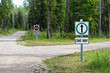 A one way and a wrong way sign by a country road intersection