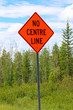 A no centre line sign with trees in the background