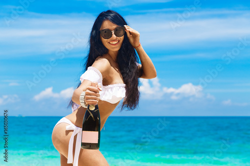 Beautiful brunette girl with long hair in bikini with bottle of champagne on a tropical beach. Summer vacation concept. © frolova_elena