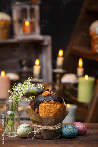 Festive cupcake with a bouquet of valley lilies on a background of candles