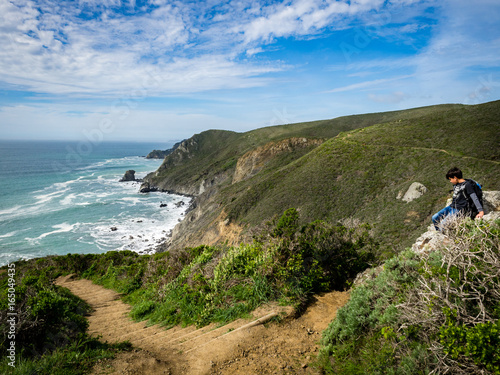 10 year old boy climbing on rocks beside trail, Pirates Cove Trail, Marin Headla Poster