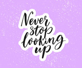 Never stop looking up. Inspirational quote, brush calligraphy on purple background.