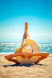 Back view of woman in hat lying and relaxing on beach with legs up. - 165101807