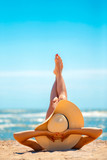 Back view of woman in hat lying and relaxing on beach with legs up.