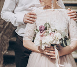 stylish wedding couple with bouquet. modern bride and groom holding fashionable bouquet at old stairs at castle. fine art wedding photo, romantic moment - 165103294