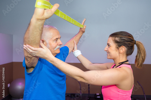 physiotherapist working with senior man using strap Poster