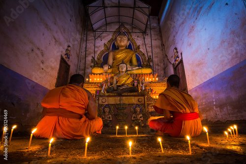 Novice Monk meditating fire candles to the Buddha in thailand Poster