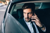 Fototapety Businessman travelling by taxi and making phone call