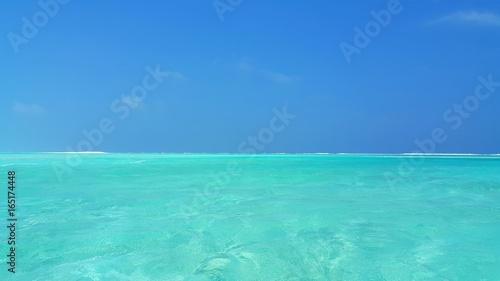 P00465 Maldives beautiful white sandy beach background on sunny tropical paradise island with aqua blue sky sea water ocean 4k