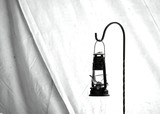 Black and white, old, civil war times gas lantern hanging at the entrance of a civil war reenactment Shelter Tent in Duncans Mills, California, USA
