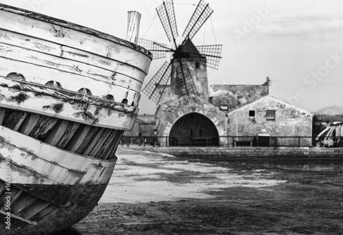 Plakat Dettagli barca in primo piano con mulino a vento sullo sfondo nella salina di Tr