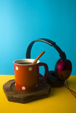 red hot coffee mug and spoon and music headphone with colorful background