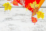 Autumn background with colored different leaves of paper on a wooden background. Children's art project, craft for children. Craft for kids.