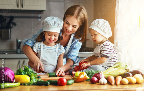 Leinwandbild Motiv Healthy eating. Happy family mother and children prepares  vegetable salad