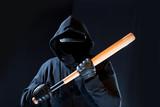 ein maskierter Mann mit Kapuze hält einen Baseballschläger in seinen Händen - 165240090