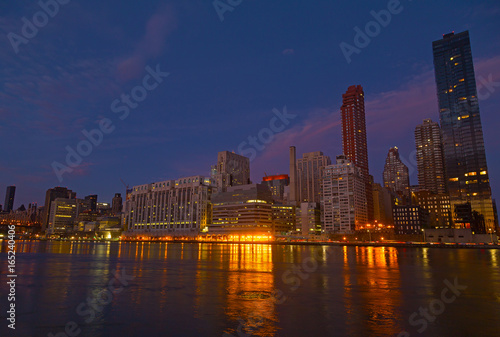 Deurstickers New York Manhattan panorama at dusk as seen from Roosevelt Island in New York, USA. New York night scene with East River waterfront illuminated buildings.