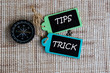 TIPS & TRICK inscription written on paper tag, compass on old wooden background.