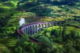 Glenfinnan Railway Viaduct in Scotland with a steam train - 165258831