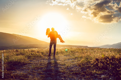 Young Guy Hands On His Girlfriend On Picturesque Sunset Background Poster