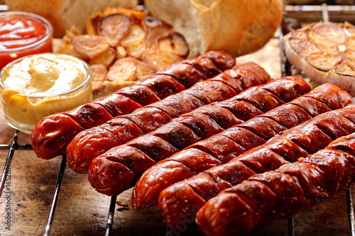 Grilled sausages with sauce ketchup and mustard on metal grate - 165285616