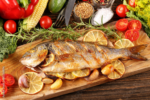 Roasted dorada fish with vegetables on wooden background - 165286896