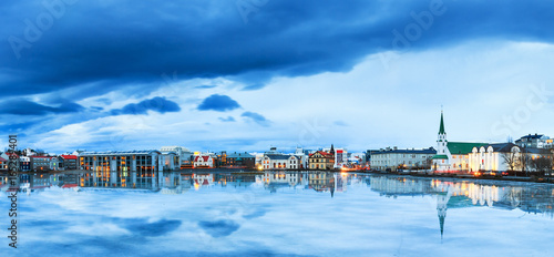 Foto op Aluminium Toronto Beautiful panorama of the skyline cityscape of Reykjavik, reflected in lake Tjornin at the blue hour in winter