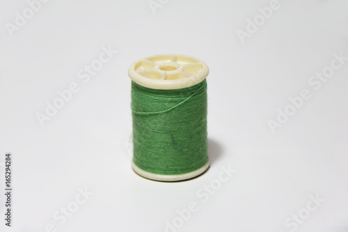 Green thread in the thread roll on white background Poster