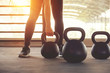 Fitness training with kettlebell in sport gym with sunlight effect.