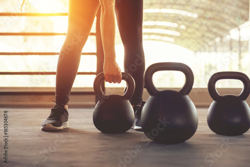 Wall mural Fitness training with kettlebell in sport gym with sunlight effect.