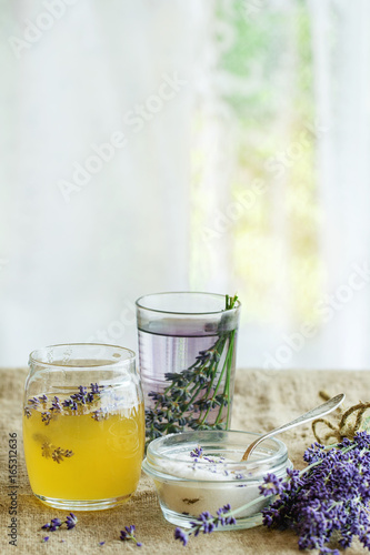 Organic raw honey, white sugar in glass jars, glass of water flavored with lavender flowers, standing on table with sackcloth. Rustic style, day light