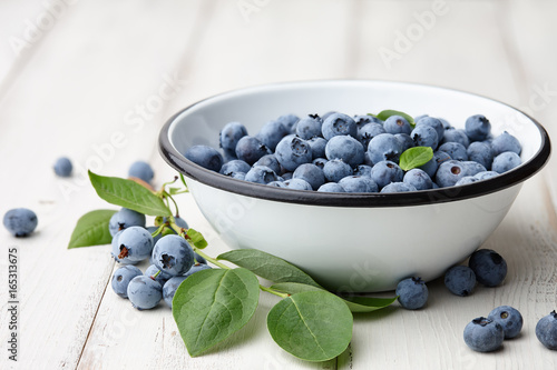 Fresh ripe blueberries with leaves in bowl on white wooden planks - 165313675
