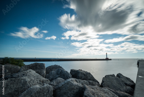 Fotobehang Toronto signal light and jetty with rocky coast in the harbor in Oakville near Toronto on Lake Ontario