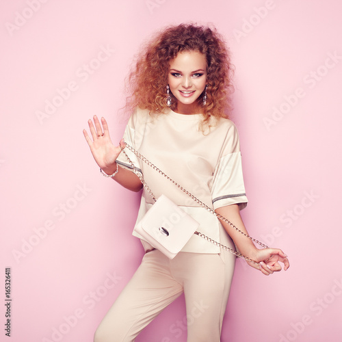 Fashion portrait of woman in summer outfit. Girl posing on pink background. Pink handbag. Stylish curly hairstyle. Glamour lady