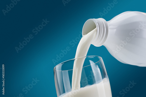 Foto op Plexiglas Milkshake Pouring fresh milk into a glass