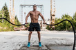 Man exercising with ropes in an abandoned construction site