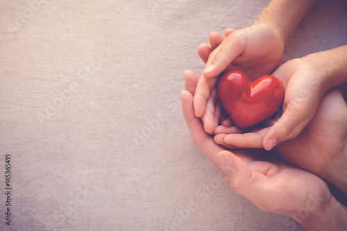 Leinwandbild Motiv adult and child hands holiding red heart, health care love and family concept