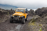 A curly-haired man is looking away driving an offroad yelow vehicle at the top of a valley with dark ground road