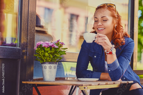 Wall mural Portrait of redhead female drinks coffee in a cafe.