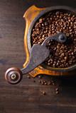 Old coffee grinder and roasted coffee beans .