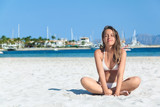Young woman sitting on the white sand beach of Alcudia, Mallorca, Spain