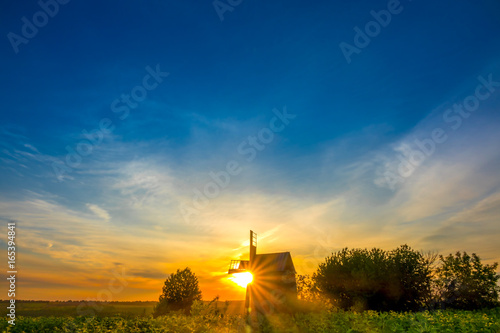 fototapeta na ścianę Sunrise and an Old Wooden Windmill