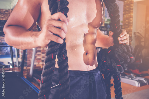 body builder men with battle ropes exercise in the fitness gym.