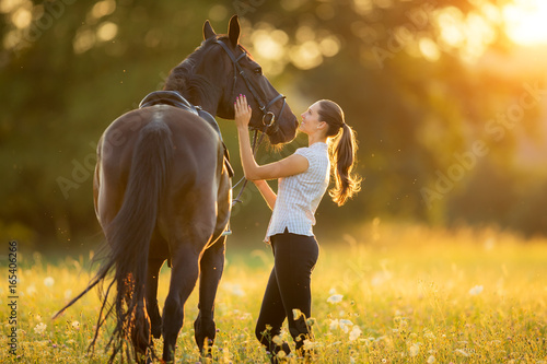 Young woman with her horse in evening sunset light - 165406266