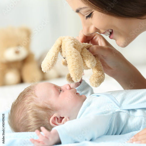 Mother playing with her baby with a teddy - 165419638