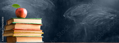 Fototapeta School accessories, books and fresh apple against chalkboard
