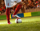 Soccer player with red socks preparing for free kick.