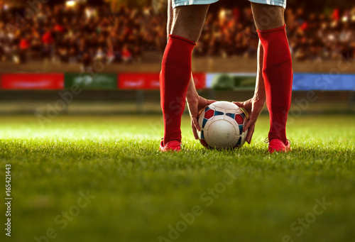 Soccer player with red socks preparing for free kick. Poster